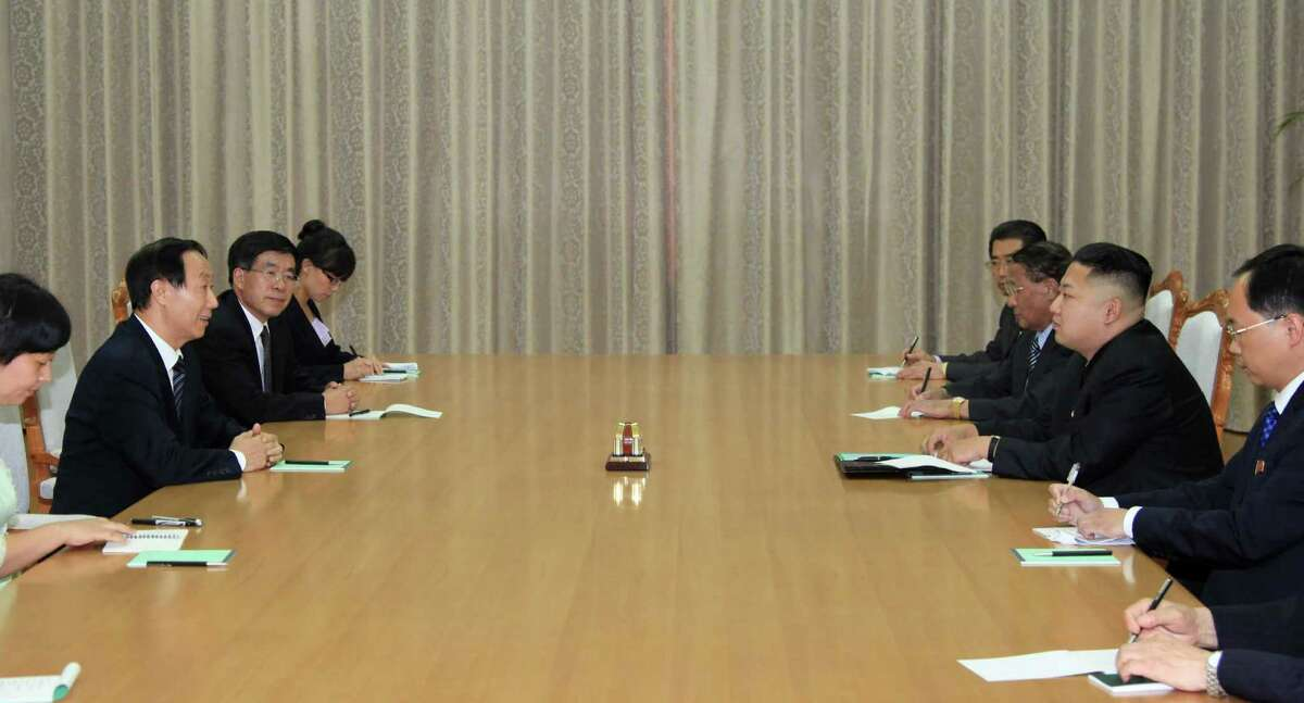 In this photo taken Thursday, Aug. 2, 2012, North Korean leader Kim Jong Un, second from right, talks with Wang Jiarui, second from left, head of the International Department of the Chinese Communist Party, during a meeting in Pyongyang, North Korea. Kim met with senior political officials from China in a sign that he may be turning his attention to foreign diplomacy. (AP Photo/Xinhua, Zhang Li) NO SALES