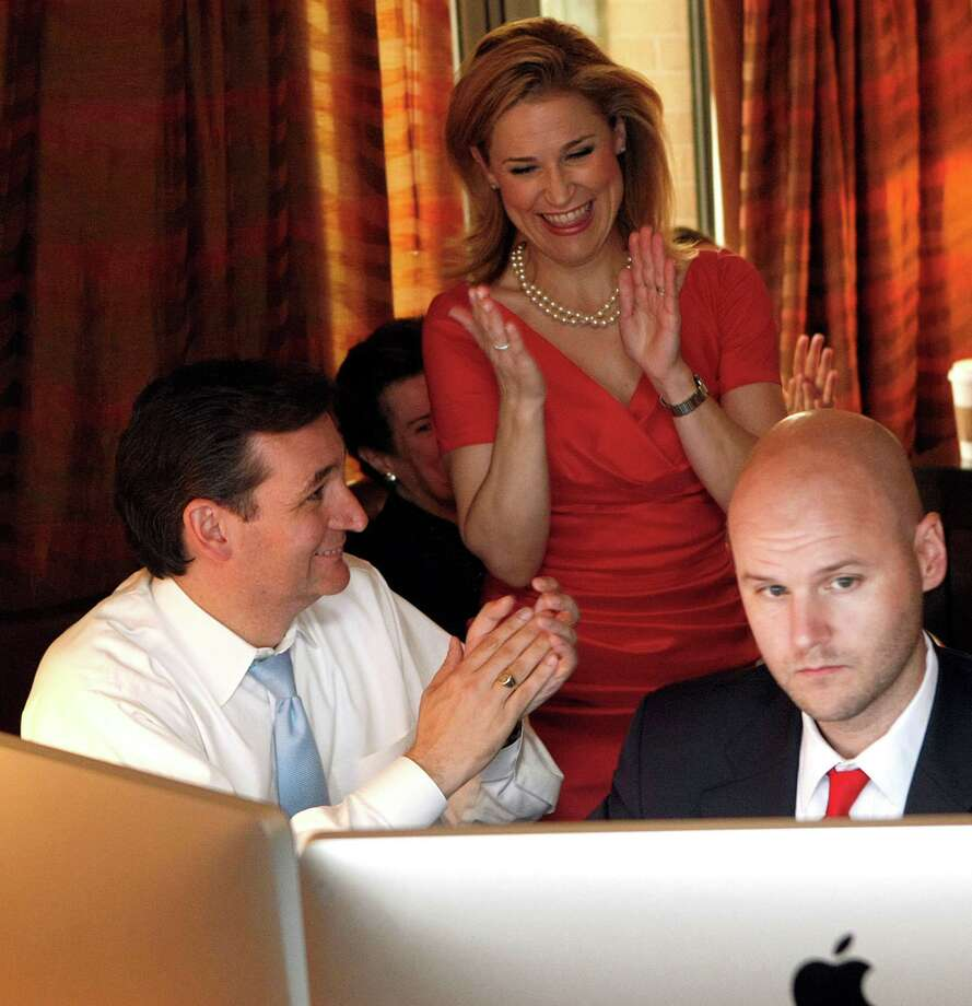Ted Cruz, left, watches runoff returns via the Internet with his wife, Heidi, and general consultant Jason Johnson on Tuesday night in Houston. Photo: Johnny Hanson / © 2012  Houston Chronicle