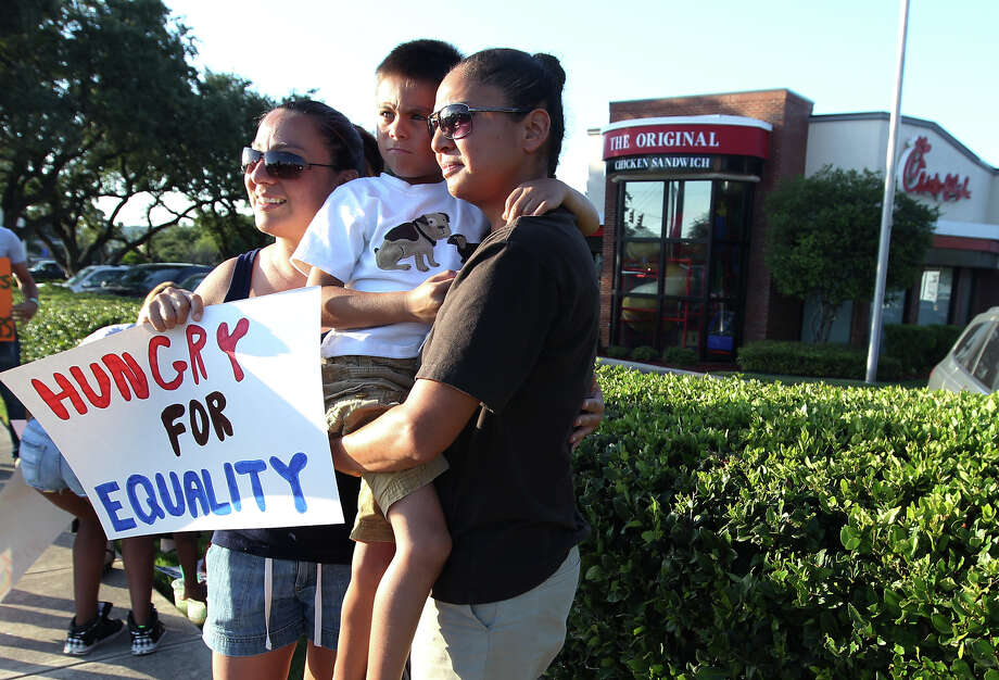 Cristina Rios (left) and her partner Hope Molina along with their six-year-old son, Jude, join in a demonstration in front of a Chick-fil-A on Friday, August 3, 2012. Local pro-same sex activists and supporters demonstrated in front of the Chick-fil-A on Bandera Road and Loop 1604. About 20 demonstrators showed up with signs as a reaction to recent statements made by Chick-fil-A president Dan Cathy on marriage based on his Christian faith. The group of same-sex marriage supporters was significantly smaller than an earlier turnout of patrons which filled the restaurants in support of Cathy and his right to free speech. Photo: Kin Man Hui, San Antonio Express-News / ©2012 San Antonio Express-News