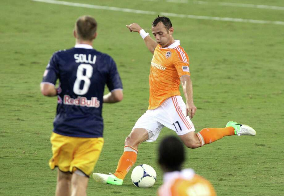 Houston Dynamo midfielder Brad Davis (11) dribbles past New York Red Bulls midfielder Jan Gunnar Solli (8) during the first half of a MLS soccer game at BBVA Compass Stadium Friday, Aug. 3, 2012, in Houston, TX. ( J. Patric Schneider / For the Chronicle ) Photo: J. Patric Schneider, Houston Chronicle / © 2012 Houston Chronicle
