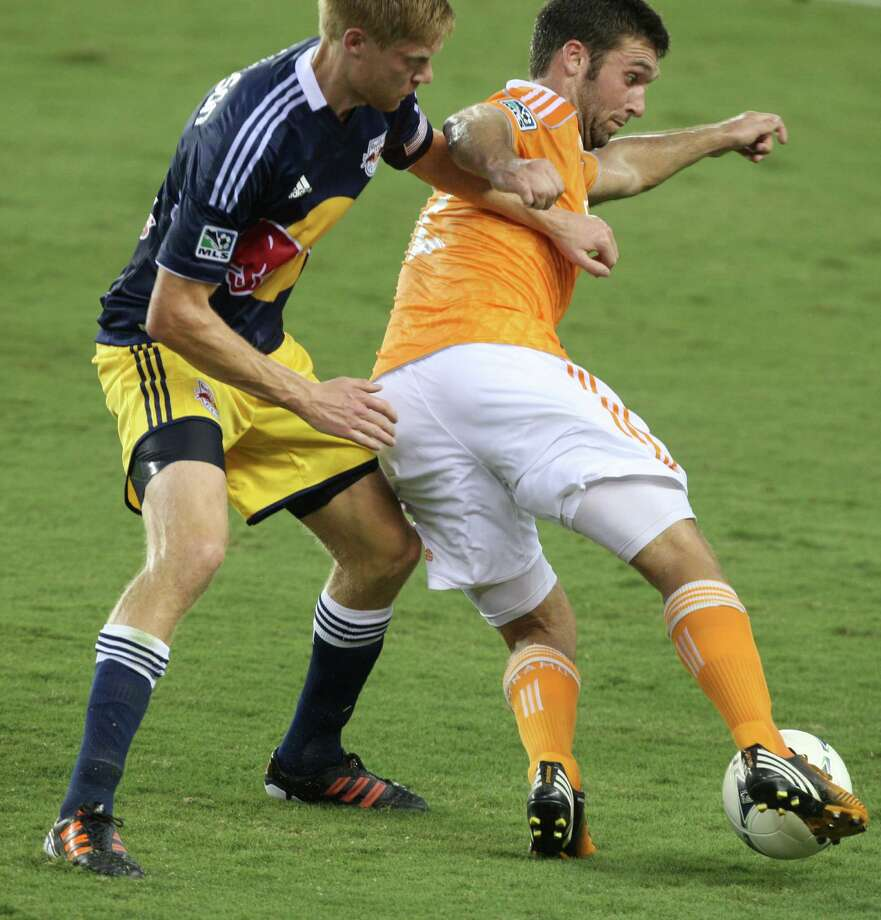 Houston Dynamo forward Will Bruin (12) dribbles past New York Red Bulls defender Markus Holgersson (5) during the first half of a MLS soccer game at BBVA Compass Stadium Friday, Aug. 3, 2012, in Houston, TX. ( J. Patric Schneider / For the Chronicle ) Photo: J. Patric Schneider, Houston Chronicle / © 2012 Houston Chronicle
