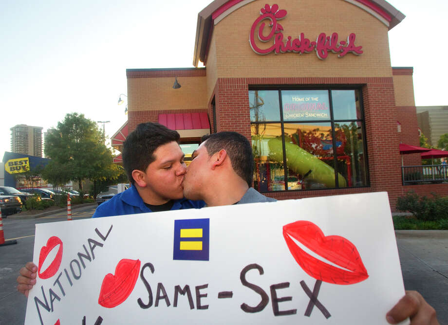 Miguel Martinez, left, kisses partner of five years, Sergio Andrade, right, during National Same Sex Kiss Day at Chick-fil-A on Richmond Avenue in support for love, equality, and the real definition of family Friday, Aug. 3, 2012, in Houston. Andrade said that they want to have the freedom to go down to city hall and get married with family and friends instead of traveling to another state. Photo: Cody Duty, Houston Chronicle / © 2011 Houston Chronicle