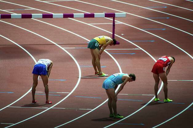 Competitors in a preliminary round heat of the men's 3000-meter steeple hang their head after crossing the finish line at the 2012 London Olympics on Friday, Aug. 3, 2012. Photo: Smiley N. Pool, Houston Chronicle / © 2012  Houston Chronicle