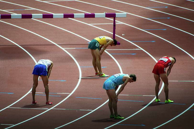 Competitors in a preliminary round heat of the men's 3000-meter steeple hang their head after crossi