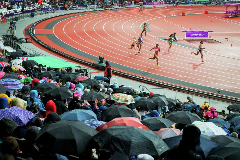 Umbrellas come out as rain falls while DeeDee Trotter of the USA runs in a first round heat of the women's 400-meters at the 2012 London Olympics on Friday, Aug. 3, 2012. Photo: Smiley N. Pool, Houston Chronicle / © 2012  Houston Chronicle