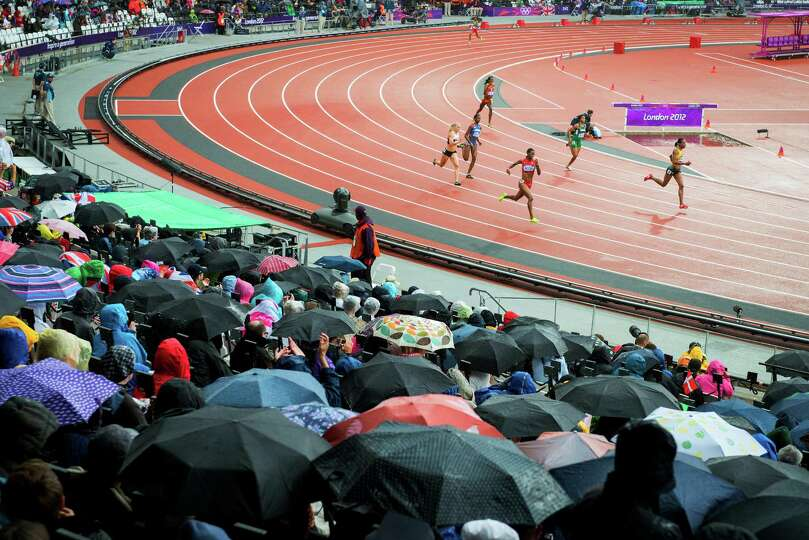 Umbrellas come out as rain falls while DeeDee Trotter of the USA runs in a first round heat of the w