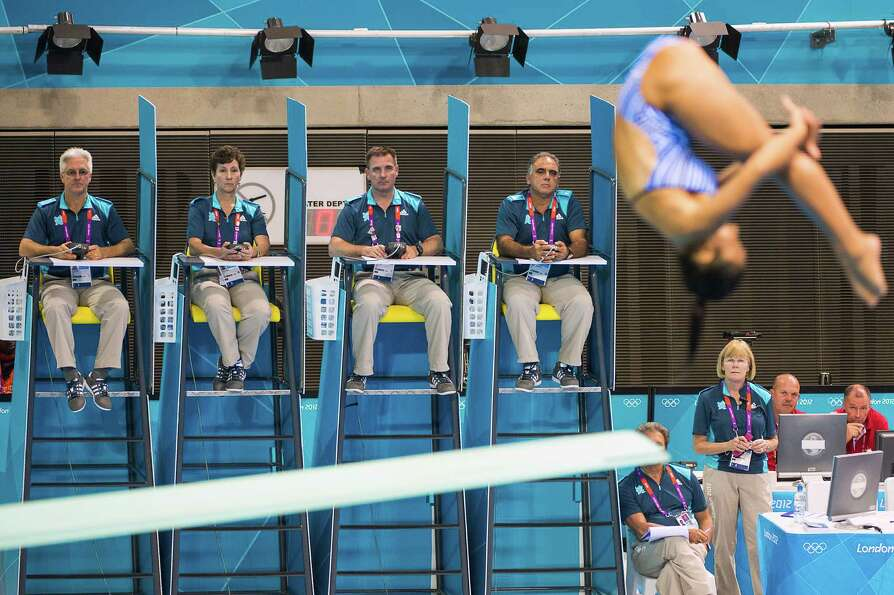 Judges keep their eye on divers during the women's 3-meter springboard diving preliminaries at the 2
