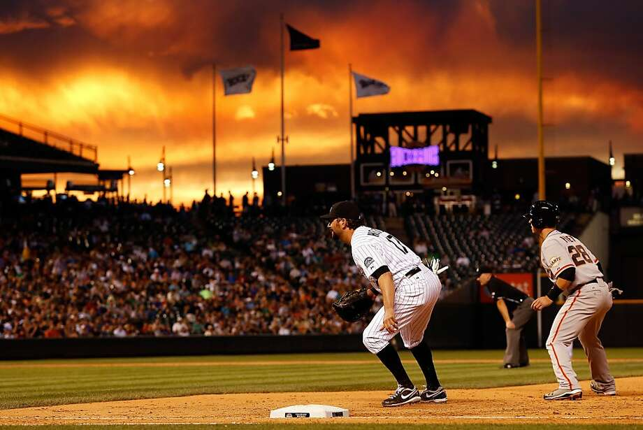 First baseman Todd Helton #17 of the Colorado Rockies plays defense and Buster Posey #28 of the San Francisco Giants leads off first base as sunset falls over the stadium at Coors Field on August 3, 2012 in Denver, Colorado.  (Photo by Doug Pensinger/Getty Images) Photo: Doug Pensinger, Getty Images