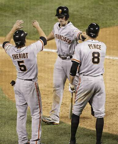 Ryan Theriot and Hunter Pence congratulate Buster Posey after his three-run homer in the Giants' six-run eighth inning. Photo: Joe Mahoney, Associated Press / SF