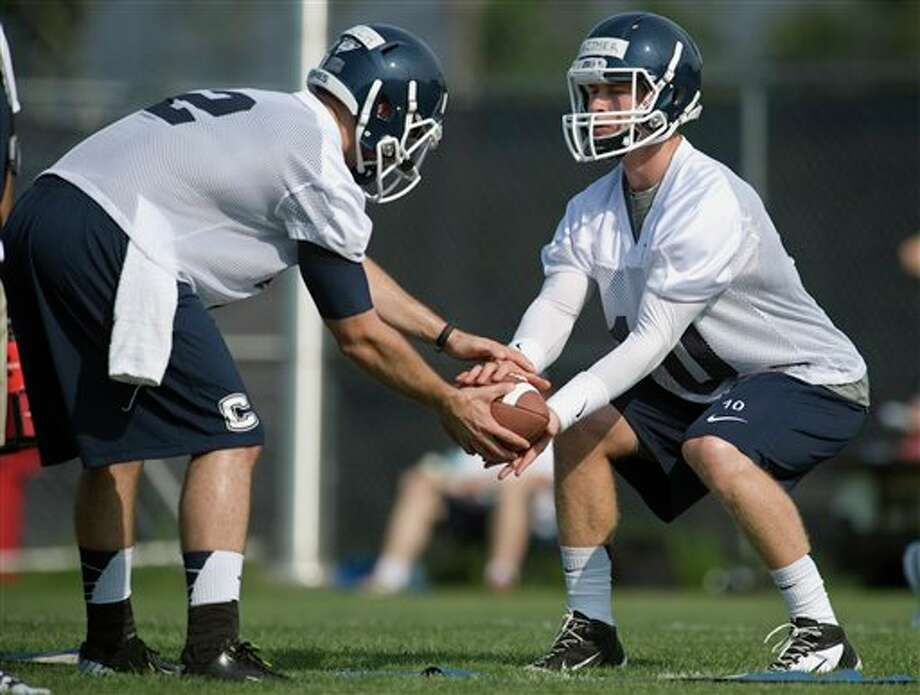 Connecticut quarterback Michael Nebrich, left, hands off to quarterback Chandler Whitmer during the first NCAA fall football practice in Storrs, Conn., Friday, Aug. 3, 2012. Connecticut's quarterback job is apparently sophomore transfer Whitmer's to lose as the Huskies begin fall practice on Friday. Last year's starter, senior Johnny McEntee will be in a group of four others trying to win the job away from Whitmer. (AP Photo/Jessica Hill)