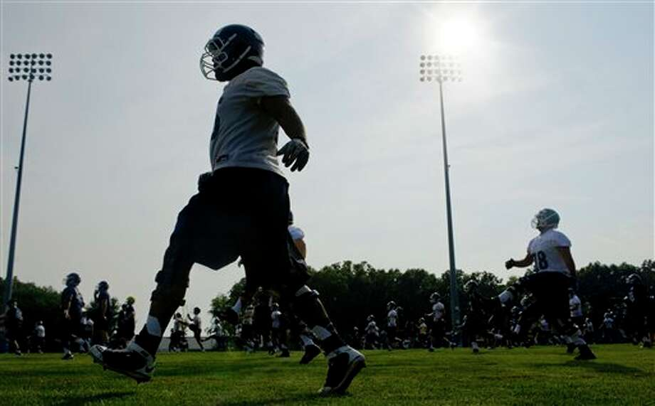 Connecticut players work out during the first NCAA fall football practice in Storrs, Conn., Friday, Aug. 3, 2012. Connecticut's quarterback job is apparently sophomore transfer Chandler Whitmer's to lose as the Huskies begin fall practice on Friday. Last year's starter, senior Johnny McEntee will be in a group of four others trying to win the job away from Whitmer. (AP Photo/Jessica Hill)