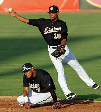 Missions shortstop Jeudy Valdez avoids his teammate Jonathan Galvez trying to get a runner at first in the second inning.  The runner was safe on the play, then the first baseman attempted a pickoff at home but the catcher missed the tagged and dropped the ball allowing a run to score as the Missions host the Frisco Roughriders at Wolff Stadium on August 3, 2012. Photo: Tom Reel, Express-News / ©2012 San Antono Express-News