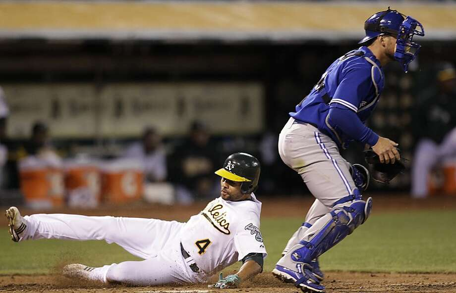 Oakland Athletics' Coco Crisp, left, slides to score past Toronto Blue Jays catcher Jeff Mathis in the fifth inning of a baseball game Friday, Aug. 3, 2012, in Oakland, Calif. Crisp scored on a sacrifice fly hit by Oakland's Josh Reddick. (AP Photo/Ben Margot) Photo: Ben Margot, Associated Press