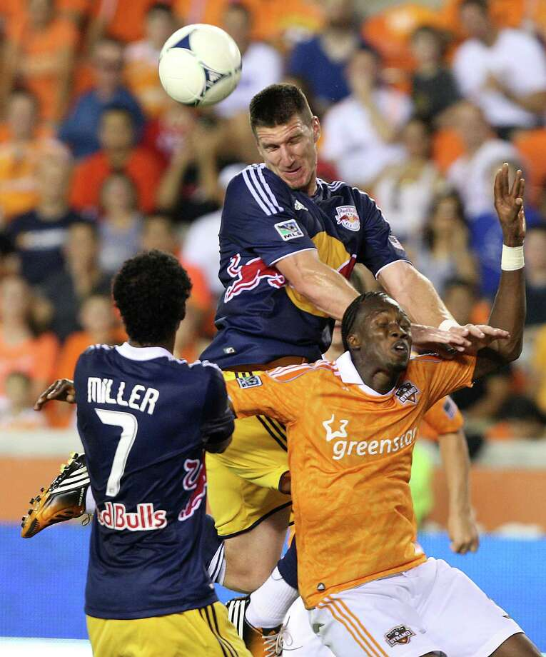 Houston Dynamo forward Macoumba Kandji (9) heads the ball with New York Red Bulls forward Kenny Cooper (33) and defender Roy Miller (7) during the second half of a MLS soccer game at BBVA Compass Stadium Friday, Aug. 3, 2012, in Houston, TX. ( J. Patric Schneider / For the Chronicle ) Photo: J. Patric Schneider, Houston Chronicle / © 2012 Houston Chronicle