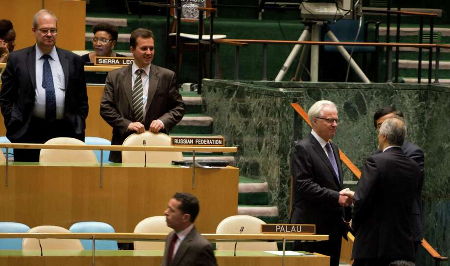 """Russia's Ambassador to the United Nations Vitaly Churkin (2nd R) talks with Syria's Ambassador to the United Nations Bashar Ja'afari before the start of the United Nations General Assembly meeting on Syria August 3, 2012 at the United Nations in New York. UN leader Ban Ki-moon said Friday that the Syria conflict has become a """"proxy war"""" and appealed to the major powers to overcome their rivalry and act to end the violence. AFP PHOTO / DON EMMERTDON EMMERT/AFP/GettyImages / AFP"""