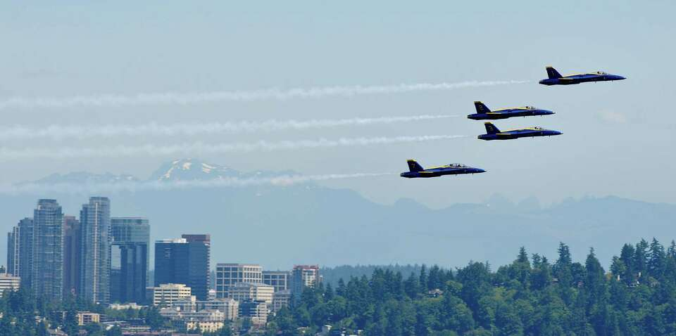 Four U.S. Navy  Blue Angels fly past the Bellevue skyline.