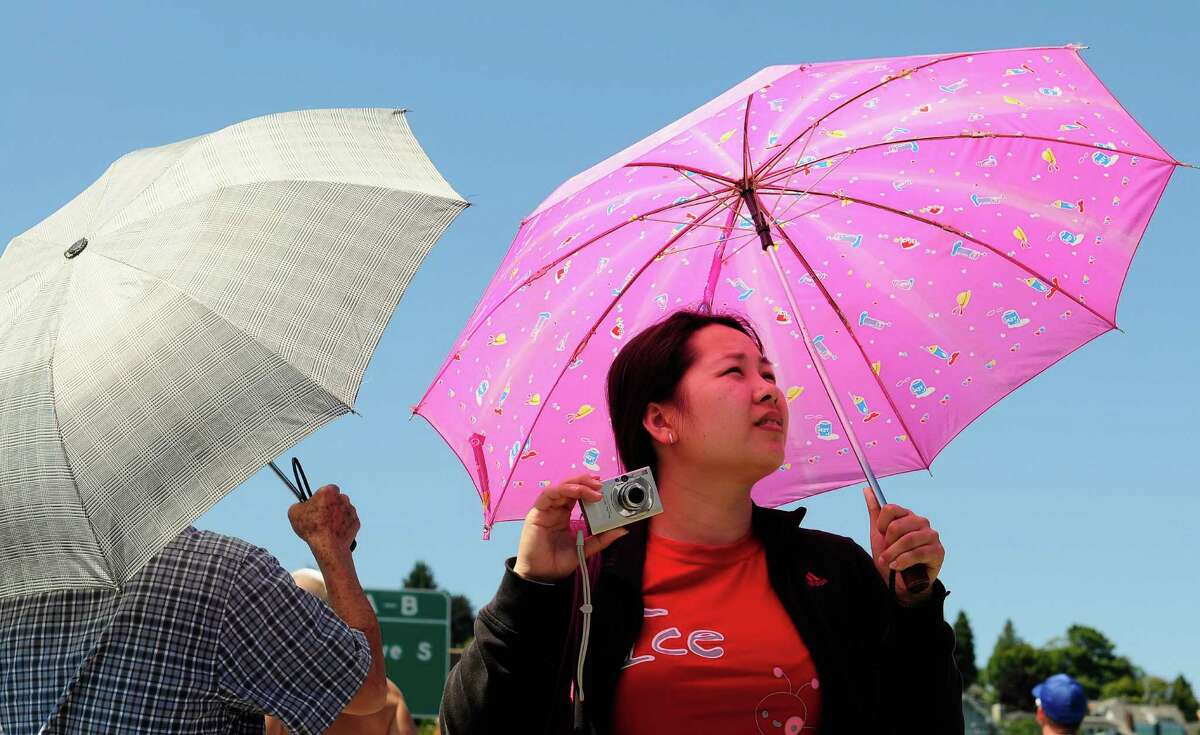 Man Ng, left, and Gina Ma, right, shield themselves from the sun with umbrellas as they watch the Navy Blue Angels demonstration over Lake Washington.