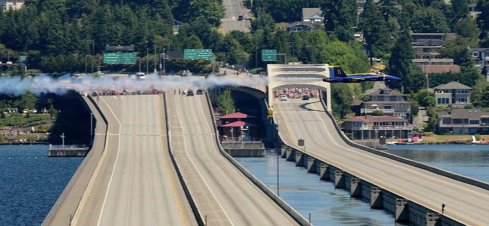 A single U.S. Navy Blue Angel screams over the I-90 bridges on Lake Washington.