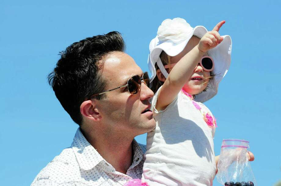 Ihly Thomason, 19 months, points at the sky as her father, Alex, looks on during a Blue Angels demonstration over Lake Washington. Photo: LINDSEY WASSON / SEATTLEPI.COM