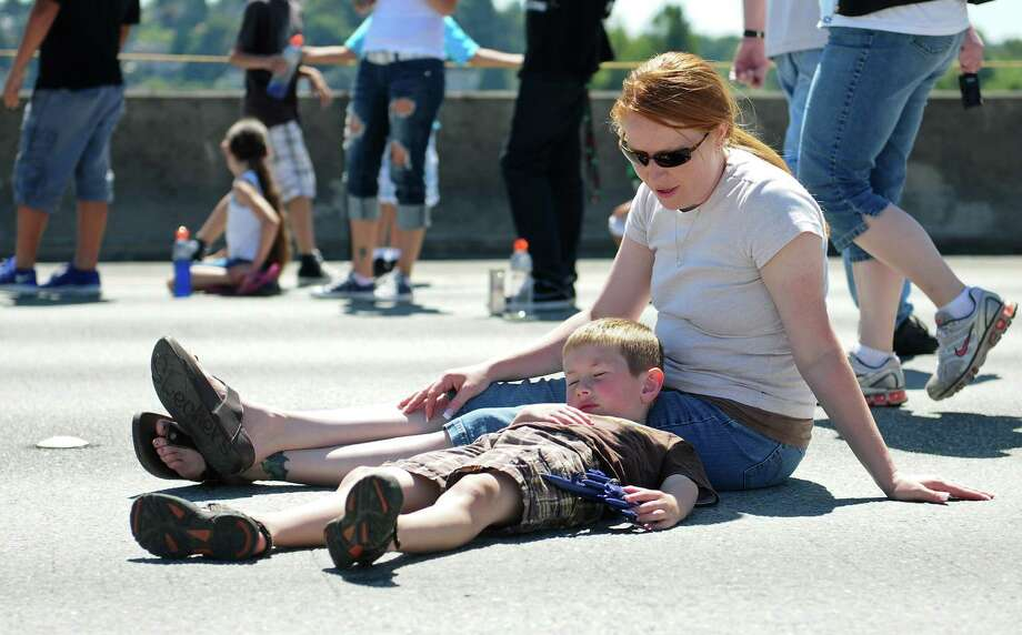 Vickie Ellis talks to a sleepy Joshua Ellis, 6, as he lies on the ground with a Blue Angels model during a Blue Angels demonstration over Lake Washington. Photo: LINDSEY WASSON / SEATTLEPI.COM