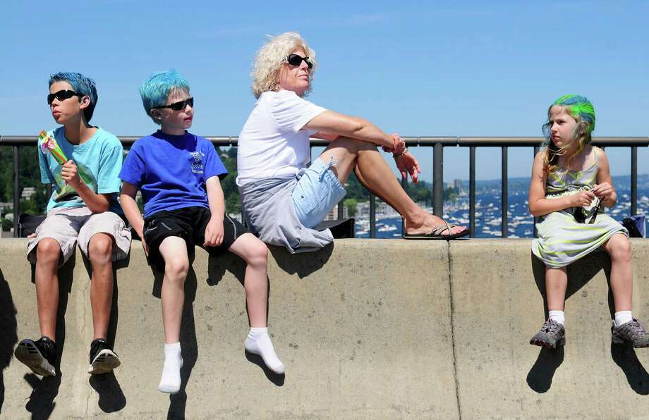 Children with colorful hair sit on a barrier on the Homer M. Hadley Memorial Bridge as they watch a Blue Angels demonstration over Lake Washington. Photo: LINDSEY WASSON / SEATTLEPI.COM