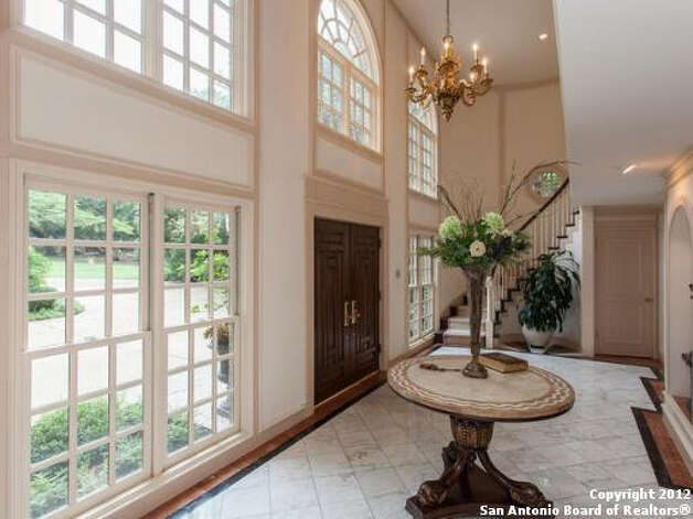 The foyer of the home features tiled flooring, a chandelier, and the stairway which winds its way to the second floor.