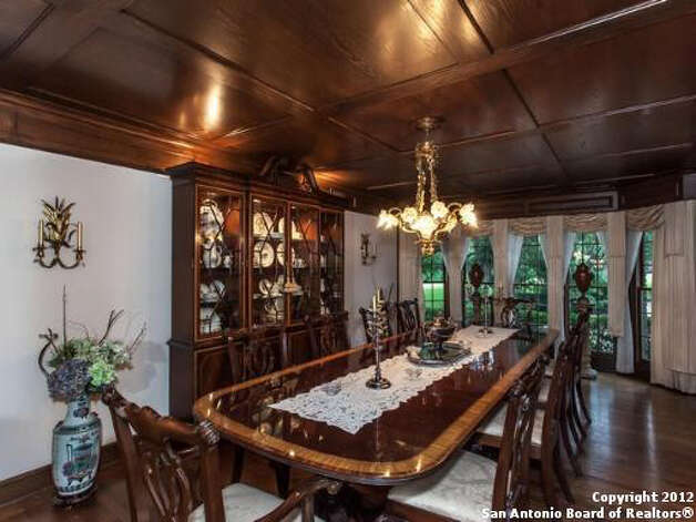 The formal dining room seats at least ten individuals and features hardwood floors and a chandelier.