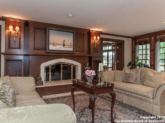 The formal living room features hardwood floors and a fireplace.