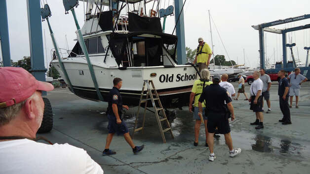 The 36-foot yacht 'Old School' is pulled from the water at Norwalk Cove Marina Friday evening after it struck a reef near Cockenoe Island about a mile offshore of Westport. Photo: Contributed Photo