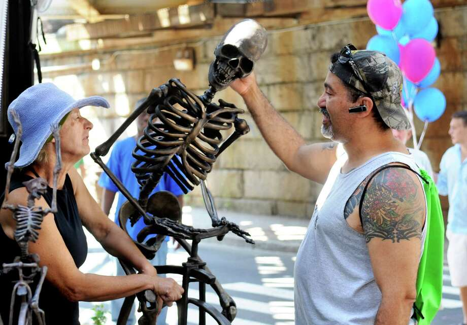 Gary Velez, right, talks to sculptor Lorann Jacobs at the 37th annual SoNo Arts Celebration in downtown Norwalk on Saturday, August 4, 2012. Photo: Lindsay Niegelberg / Stamford Advocate