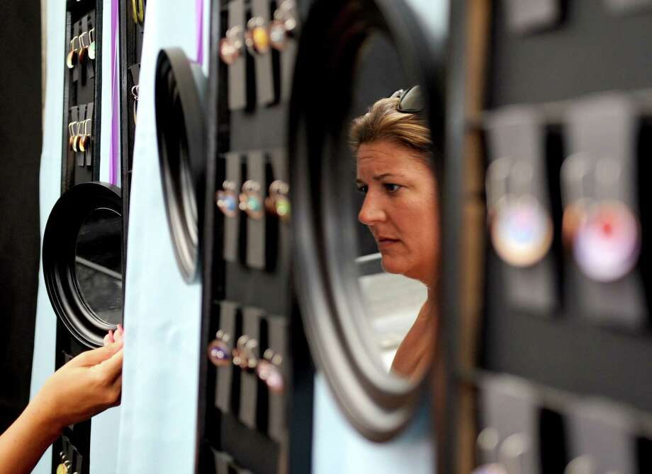Jill Morgenstein is reflected in a mirror as she looks at jewelry at the Jewelry by Lanni booth at the 37th annual SoNo Arts Celebration in downtown Norwalk on Saturday, August 4, 2012. Photo: Lindsay Niegelberg / Stamford Advocate