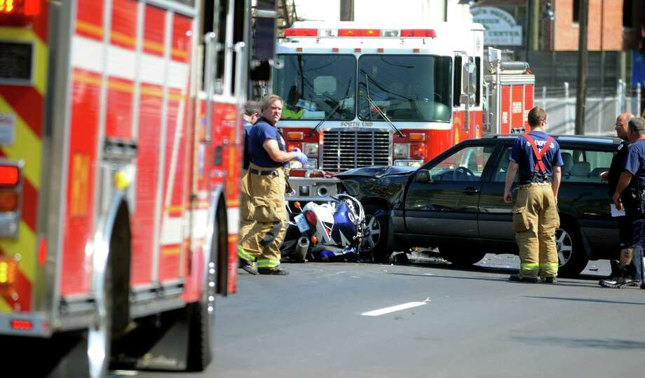 A Volvo and Suzuki motorcycle sit on Canal Street after being involved in a crash in front of Fairway Market after which the driver of the motorcycle was transported to Stamford Hospital on Saturday, August 4, 2012. Photo: Lindsay Niegelberg / Stamford Advocate