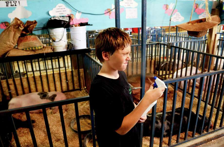 Logan Bell, 10, cools down during the Ozaukee County Fair in Cedarburg, Wis., Aug. 1, 2012. Many farming families have gone ahead with 4-H projects, like the raising of a cow or the special watering of a prized gourd, for fairs they had committed to months before extreme heat and drought struck. Photo: DARREN HAUCK, New York Times / NYTNS