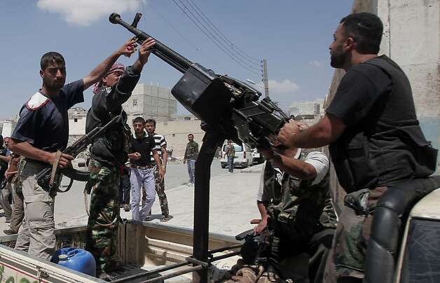 Syrian rebel fighters stand around an anti-aircraft machinegun mounted on a truck in the northern city of Aleppo on August 4, 2012. Syria's armed forces pounded the rebel-held Salaheddin district of Aleppo from the air and ground, with violence also raging in the Shaar and Sukkari districts, according to reporters in the area and a rebel commander. Photo: Ahmad Gharabli, AFP/Getty Images / SF