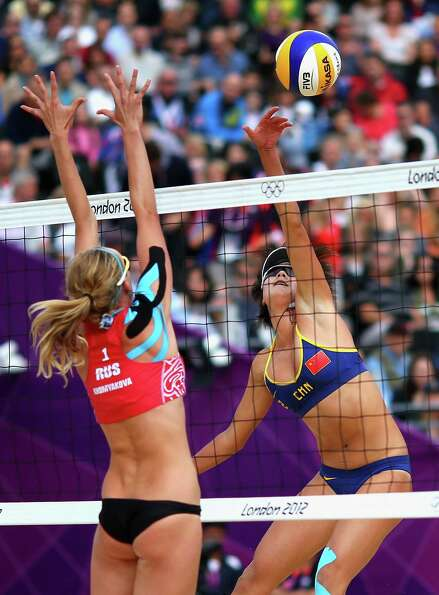 Xi Zhang of China spikes past Ekaterina Khomyakova of Russia during the Women's Beach Volleyball Rou
