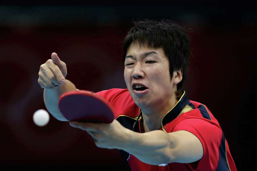Jun Mizutani of Japan completes during Men's Team Table Tennis first round match against team of Can
