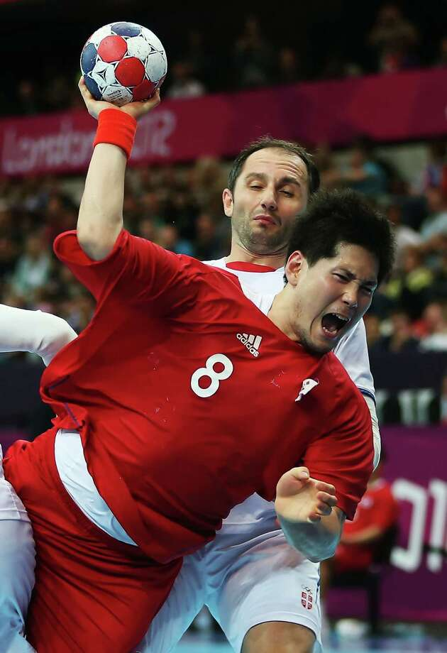Junggeu Park #8 of Korea shoots while defended by Alem Toskic #11 of Serbia during the Men's Preliminaries Group B match between Korea and Serbia at the Copper Box. Photo: Jeff Gross, Getty Images / 2012 Getty Images