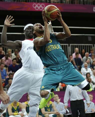 Australia's Patrick Mills drives to the basket past Britain's Pops Mensah-Bonsu during a men's basketball game at the 2012 Summer Olympics, Saturday, Aug. 4, 2012, in London. (AP Photo/Charles Krupa) (Associated Press)