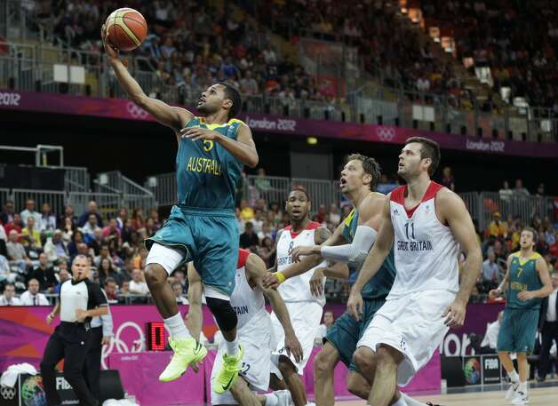 Australia's Patrick Mills, left, drives to the basket against Britain during a men's basketball game at the 2012 Summer Olympics, Saturday, Aug. 4, 2012, in London. (AP Photo/Charles Krupa) (Associated Press)
