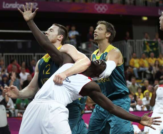 Australia's Aron Baynes, left, and David Andersen keep Britain's Pops Mensah-Bonsu, center, away from a rebound during a men's basketball game at the 2012 Summer Olympics, Saturday, Aug. 4, 2012, in London. (AP Photo/Charles Krupa) (Associated Press)