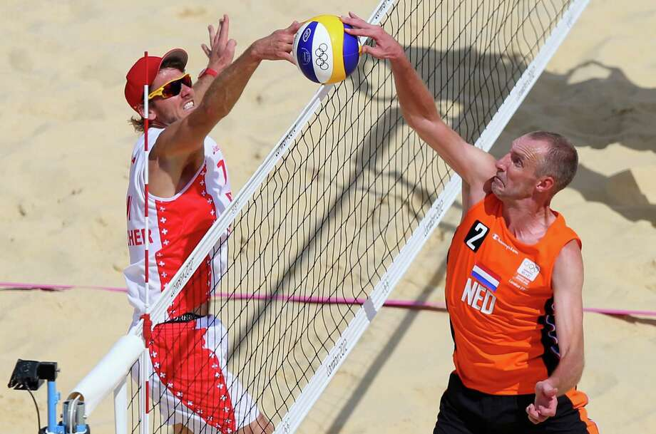 Rich Schuil of Netherlands and Patrick Heuscher of Switzerland contest the ball at the net during the Men's Beach Volleyball Round of 16 match between Netherlands and Switzerland at Horse Guards Parade. Photo: Ryan Pierse, Getty Images / 2012 Getty Images