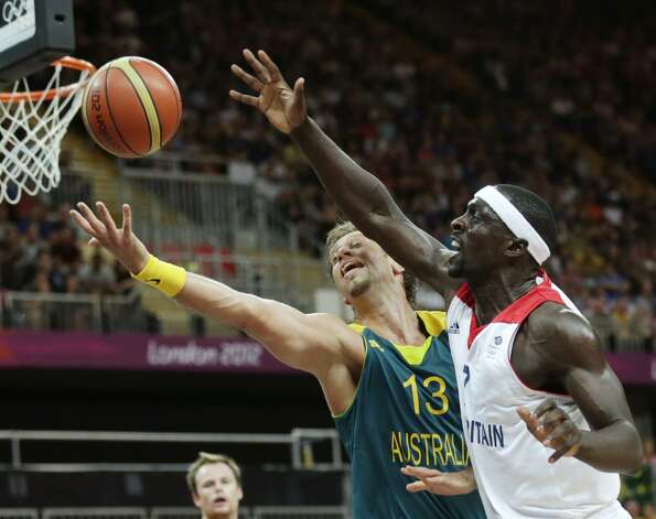 Britain's Pops Mensah-Bonsu, right, and Australia's David Andersen reach for a rebound during a men's basketball game at the 2012 Summer Olympics, Saturday, Aug. 4, 2012, in London. (AP Photo/Charles Krupa) (Associated Press)