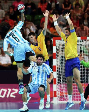 Diego Esteban Simonet #6 of Argentina shoots over teammate Sebastian Simonet #4, Kim Andersson #5 of Sweden and Tobias Karlsson #18 of Sweden during the Men's Preliminaries Group A match between Sweden and Argentina at the Copper Box. Photo: Jeff Gross, Getty Images / 2012 Getty Images