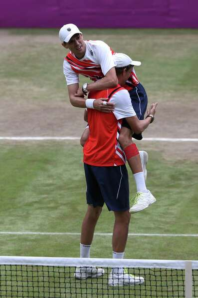 Mike Bryan (R) and  Bob Bryan (L) celebrate after defeating Jo-Wilfried Tsonga and Michael Llodra of