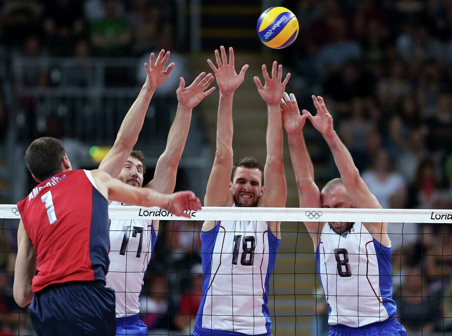 Maxim Mikhaylov #17,Alexander Volkov #18 and Sergey Tetyukhin #8 of Russia try to block a spike from Matthew Anderson #1 of the United States at Earls Court. Photo: Elsa, Getty Images / 2012 Getty Images