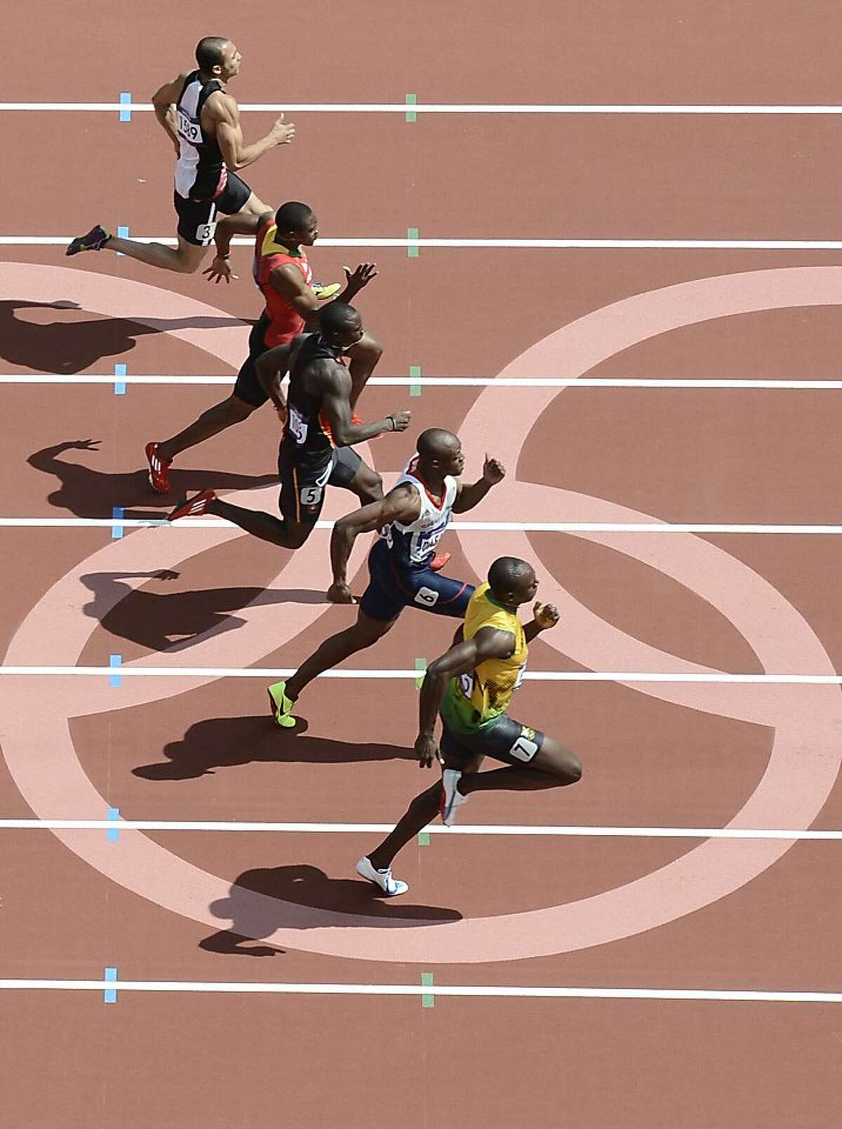 PICTURE TAKEN WITH A ROBOTIC CAMERA (From bottom) Jamaica's Usain Bolt, Britain's James Dasaolu, Antigua and Barbuda's Daniel Bailey and Saint Kitts & Nevis' Jason Rogers, Egypt's Amr Ibrahim Mostafa Seoud and Guinea-Bissau's Holder da Silva compete in the men's 100m heats at the athletics event of the London 2012 Olympic Games on August 4, 2012 in London. AFP PHOTO / ANTONIN THUILLIERANTONIN THUILLIER/AFP/GettyImages