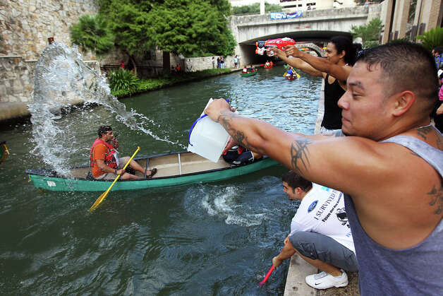 Carlos Delgado tosses a bucket of water to a group of friends in a canoe at the 44th annual Ford Canoe Challenge along the River Walk on Saturday, August 4, 2012. About 100 teams that included Boy Scouts and Girls Scouts, corporate and celebrity participants took part in one of the oldest events held on the river. Delgado and his friends made the event more challenging by adding the element of water guns and tossed water to their friends race along the course. Photo: Kin Man Hui, SAN ANTONIO EXPRESS-NEWS / ©2012 San Antonio Express-News