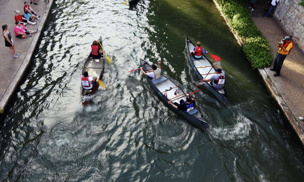 A trio of canoes are launched from the staring line at the 44th annual Ford Canoe Challenge along the River Walk on Saturday, August 4, 2012. About 100 teams that included Boy Scouts and Girls Scouts, corporate and celebrity participants took part in one of the oldest events held on the river. Photo: Kin Man Hui, SAN ANTONIO EXPRESS-NEWS / ©2012 San Antonio Express-News