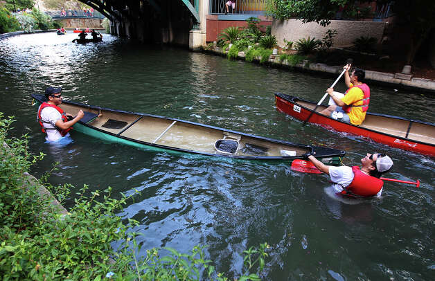Moses Munoz (left) and his paddling partner Roland Ovalle work to get back in their canoe after getting tipped over along the race course at the 44th annual Ford Canoe Challenge along the River Walk on Saturday, August 4, 2012. About 100 teams that included Boy Scouts and Girls Scouts, corporate and celebrity participants took part in one of the oldest events held on the river. Photo: Kin Man Hui, SAN ANTONIO EXPRESS-NEWS / ©2012 San Antonio Express-News