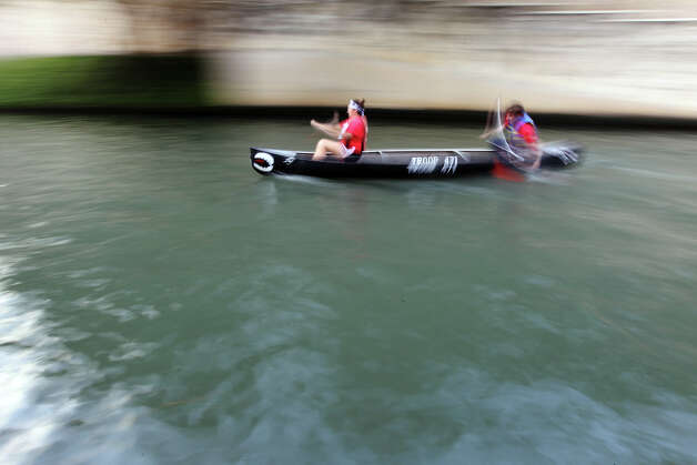 A pair of paddlers blur past the starting line as they participate in the 44th annual Ford Canoe Challenge along the River Walk on Saturday, August 4, 2012. About 100 teams that included Boy Scouts and Girls Scouts, corporate and celebrity participants took part in one of the oldest events held on the river. Photo: Kin Man Hui, SAN ANTONIO EXPRESS-NEWS / ©2012 San Antonio Express-News